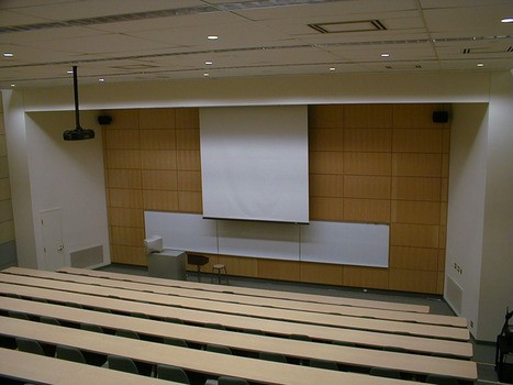 University lecture hall with ceiling mounted projector and recessed electric screen
